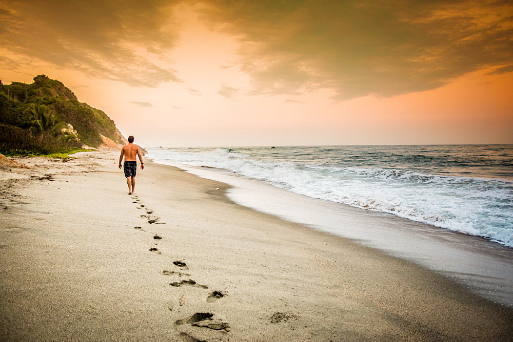 Man walking on the beach in Tayrona National Park, Colombia, South America