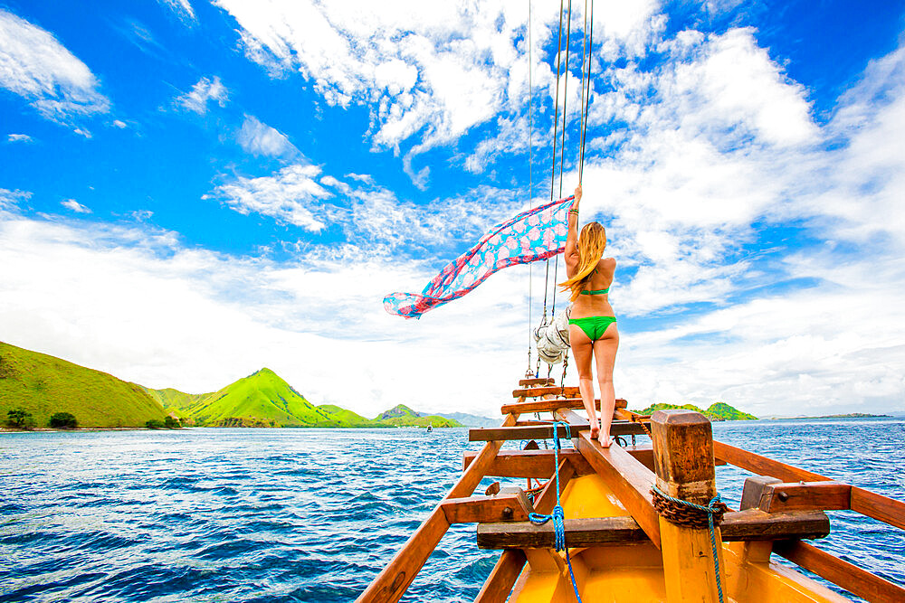 Girl perched on bow of Phinisi Boat, sailing through Komodo National Park, Indonesia, Southeast Asia, Asia - 1218-605