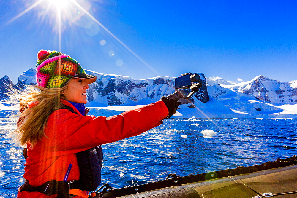 Documenting the scenic view of the glacial ice and floating icebergs in Antarctica.