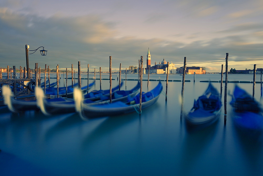 Gondolas tied to their moorings with the last light of the day illuminating San Giorgio Maggiore and its Campanile, Venice, UNESCO World Heritage Site, Veneto, Italy, Europe