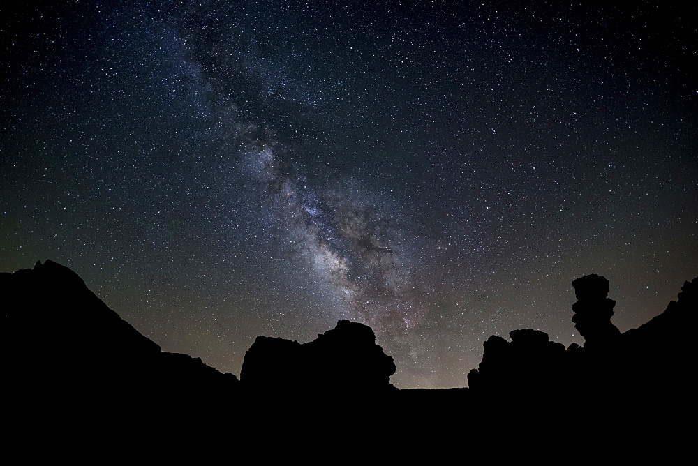 The Milky Way arches high in the night sky above Roques de Garcia in Teide National Park, UNESCO World Heritage Site, Tenerife, Canary Islands, Spain, Europe