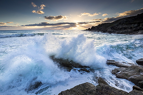 Powerful waves breaking against the cliffs at sunset at Porth Chapel near Porthcurno, South West Cornwall, England, United Kingdom, Europe