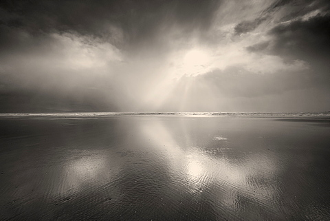 Brilliant sunshine through stormy rainshowers and racing black clouds at the expansive Llanddwyn Beach on West Anglesey, Wales, United Kingdom, Europe