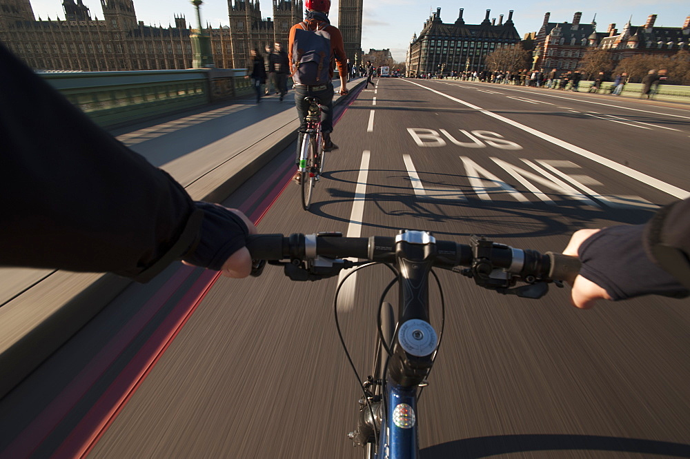 A cyclist crosses Westminster Bridge towards the Houses of Parliament, London, England, United Kingdom, Europe