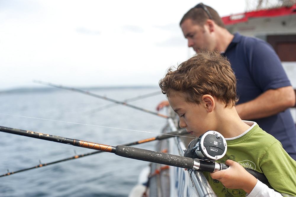 Tourists fish for Mackeral on a fishing trip from Penzance in Cornwall