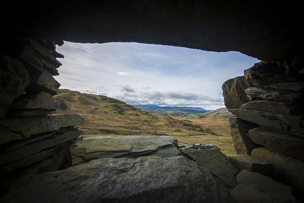 Looking through a window of a crumbling stone house on Place Fell in the English Lake District