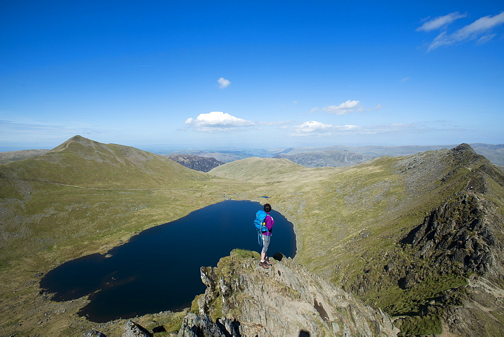 A woman stands on top of Striding Edge with a view of Red Tarn below and Ullswater in the far distance, Lake District National Park, Cumbria, England, United Kingdom, Europe