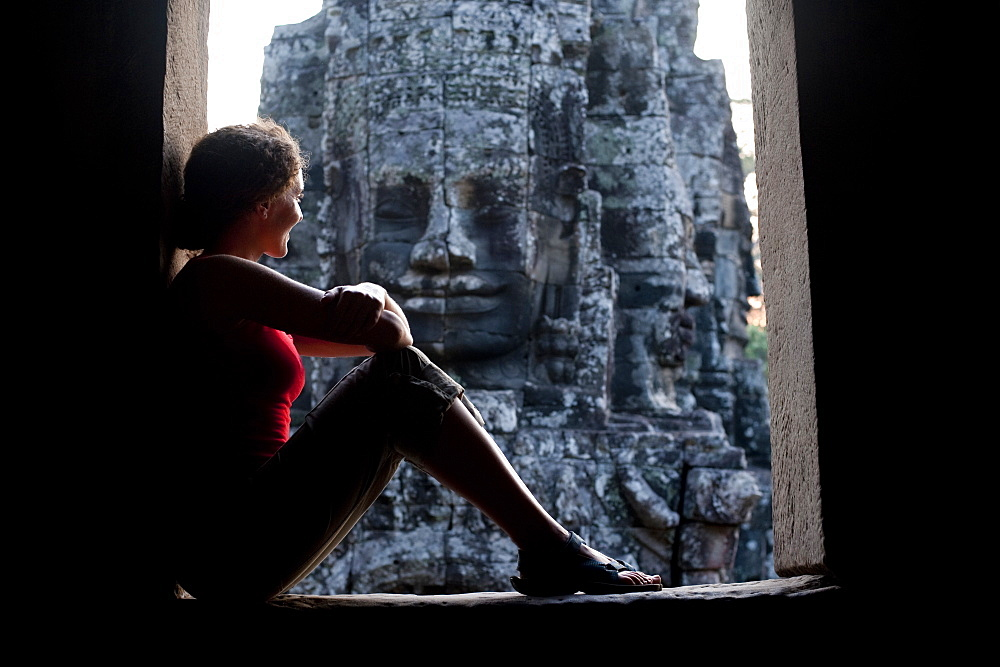 A tourist looks out from one of the doorways at the Bayon temple within Angkor Wat in Cambodia