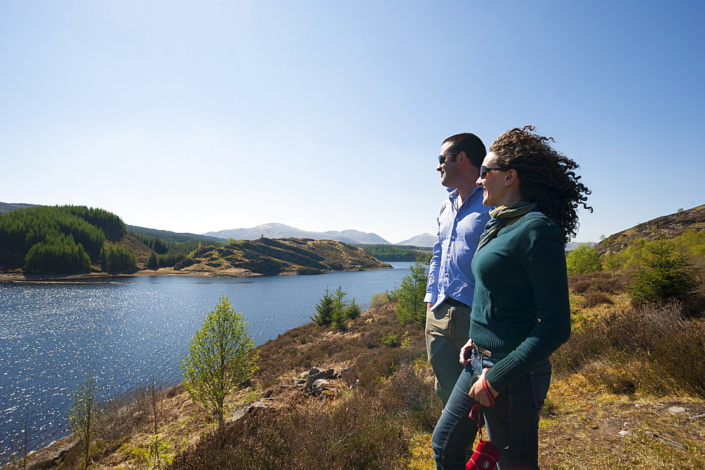 Tourists looks out across Loch Laggan in Scotland
