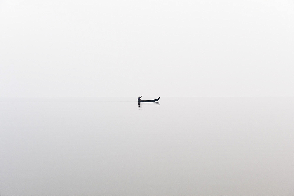 A fishing boat on a perfectly calm Indawgyi Lake in northern Myanmar on a misty afternoon, Myanmar (Burma), Asia