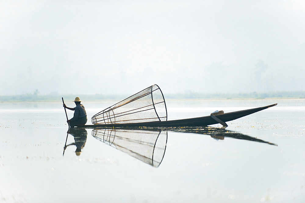 A basket fisherman on Inle Lake scans the still and shallow water for signs of life, Myanmar (Burma), Asia - 1225-1177
