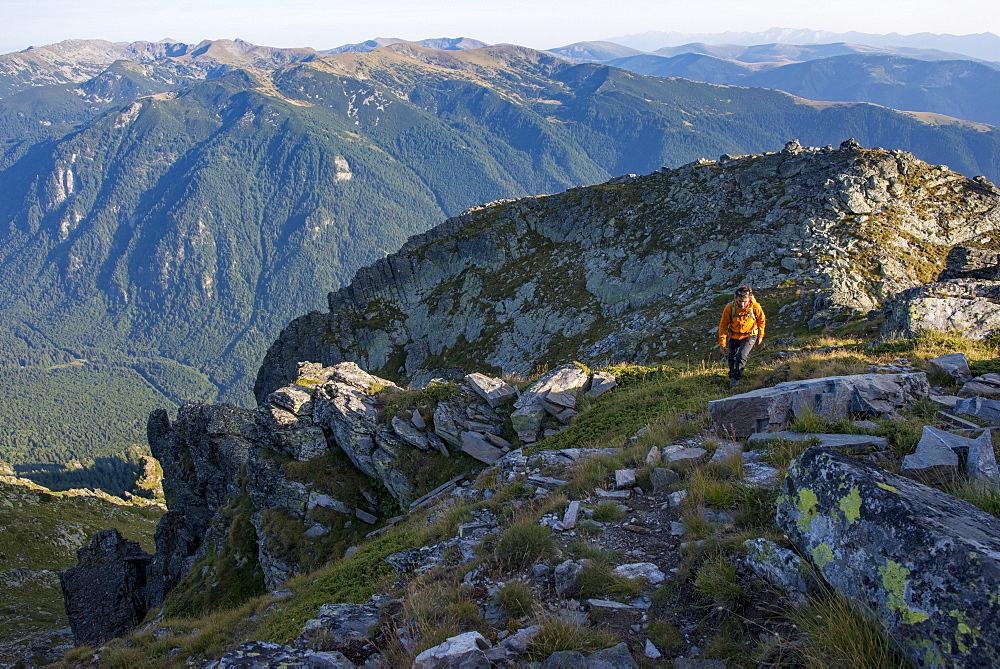 A hiker climbs along a high ridge near Maliovitsa in the Rila Mountains with distant views of valleys and hills, Bulgaria, Europe - 1225-1197