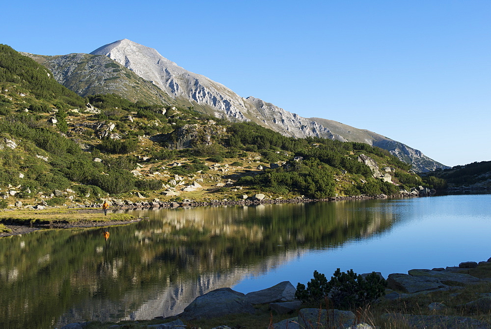 Hiking around Ribno lake with a Vihren peak distant which is the highest point in the Pirin mountains