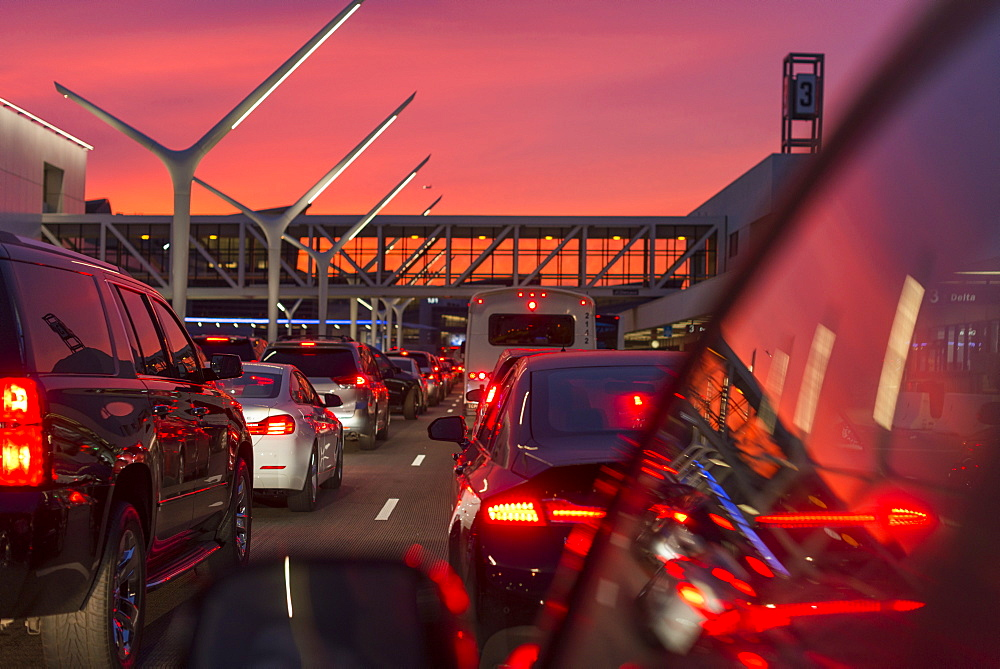 Traffic going into Los Angeles airport under a vibrant orange and pink sunset, California, United States of America, North America