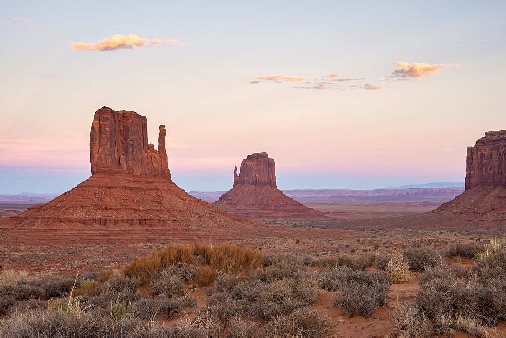 The giant sandstone buttes glowing pink at sunset in Monument Valley Navajo Tribal Park, Arizona, United States of America, North America
