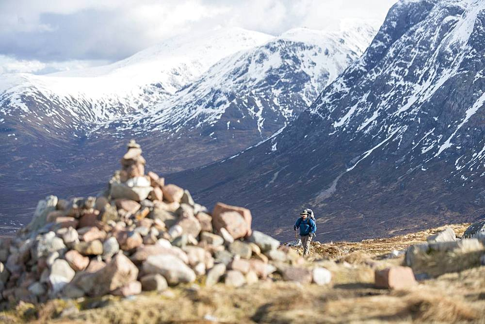 A cairn and a walker at the top of the Devils Staircase while hiking along the West Highland Way near Glencoe in the Scottish Highlands, Scotland, United Kingdom, Europe - 1225-1224