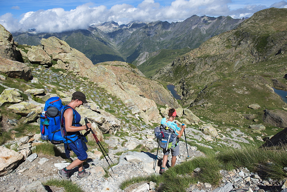 Walkers descend from the top of Pic Peyreget while hiking the GR10 trekking trail, Pyrenees Atlantiques, France, Europe