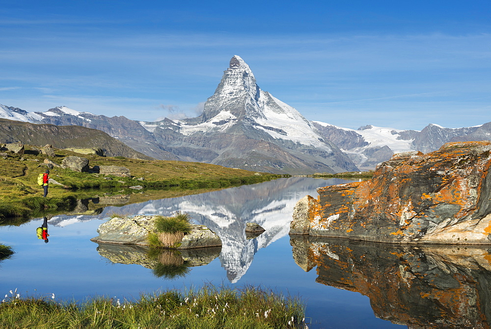 A walker hiking in the Alps takes in the view of the Matterhorn reflected in Stellisee lake at dawn, Swiss Alps, Switzerland, Europe - 1225-1275