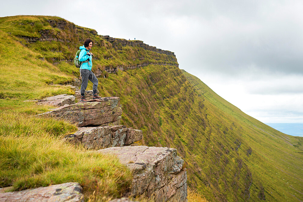A woman looks out from a high escarpment while hiking in the Brecon Beacons National Park mountain range - 1225-1308