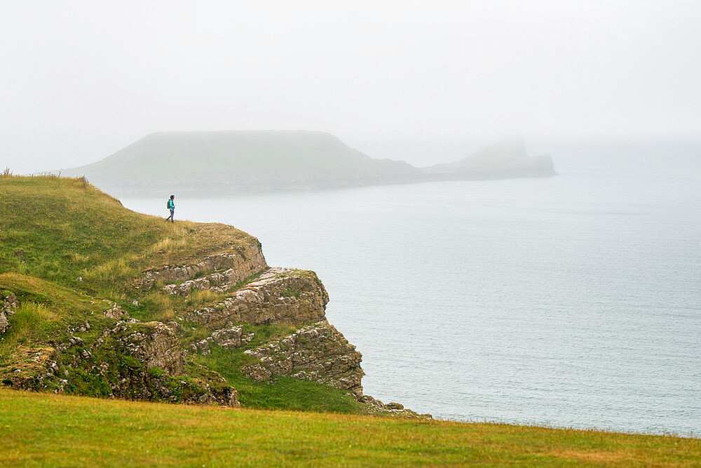A woman looking towards Worms Head on The Gower peninsula on a misty day