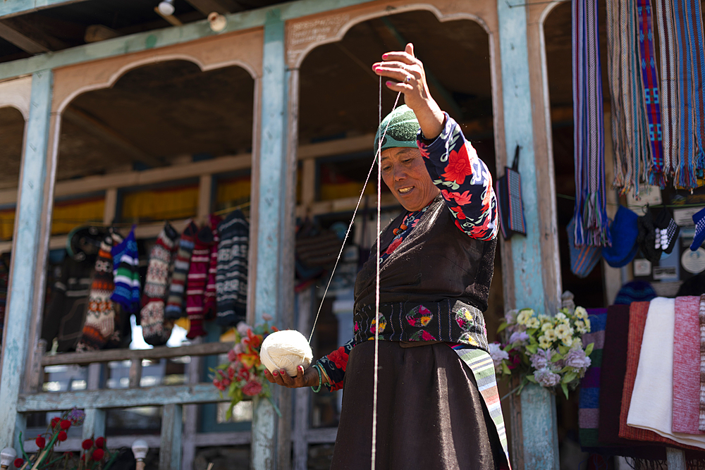 A Sherpa woman from Gosainkund spins baby Yak wool using the traditional method with a spindle, Langtang region, Nepal, Asia