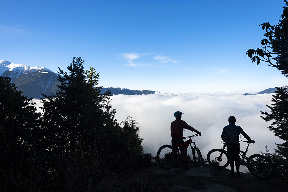 Mountain bikers look out across a valley filled with a cloud inversion in the Himalayas while biking in the Gosainkund region, Langtang region, Nepal, Asia