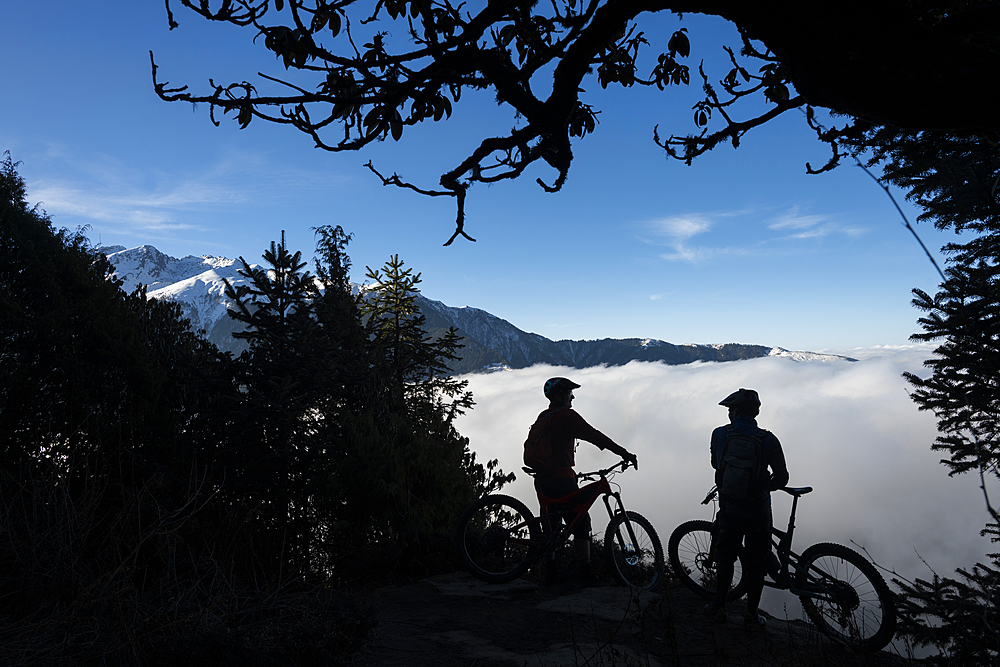 Mountain bikers look out across a valley filled with a cloud inversion in the Himalayas while biking in the Gosainkund region, Langtang region, Nepal, Asia - 1225-1348
