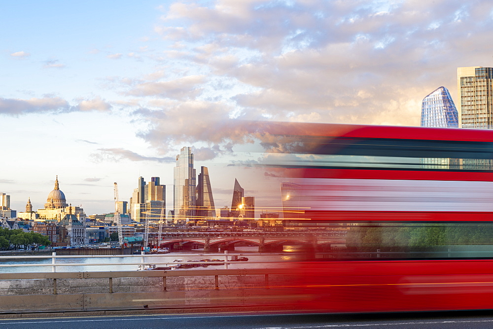 A red London bus goes past in a blur across Waterloo Bridge with the city of London and Southbank in distance