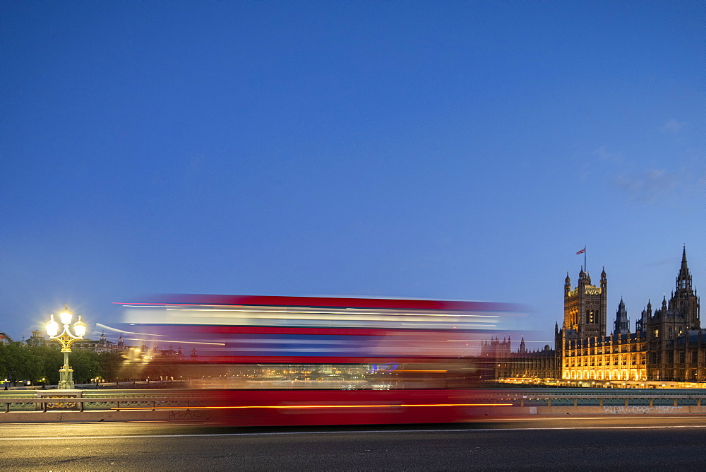 A red London bus goes past in a blur across Westminster Bridge.