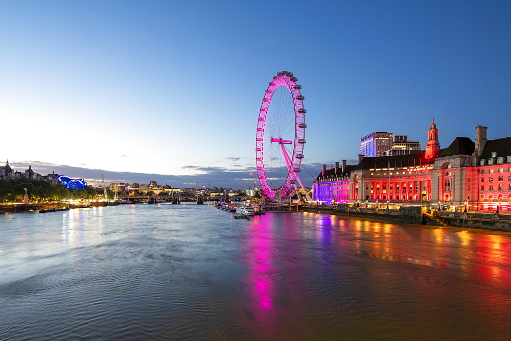 The London Eye lit up pink during blue hour