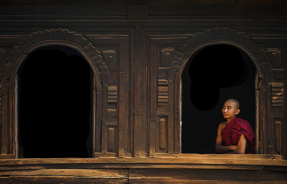 A monk looks out from the window of a wooden monastery near Bagan (Pagan), Myanmar (Burma), Asia