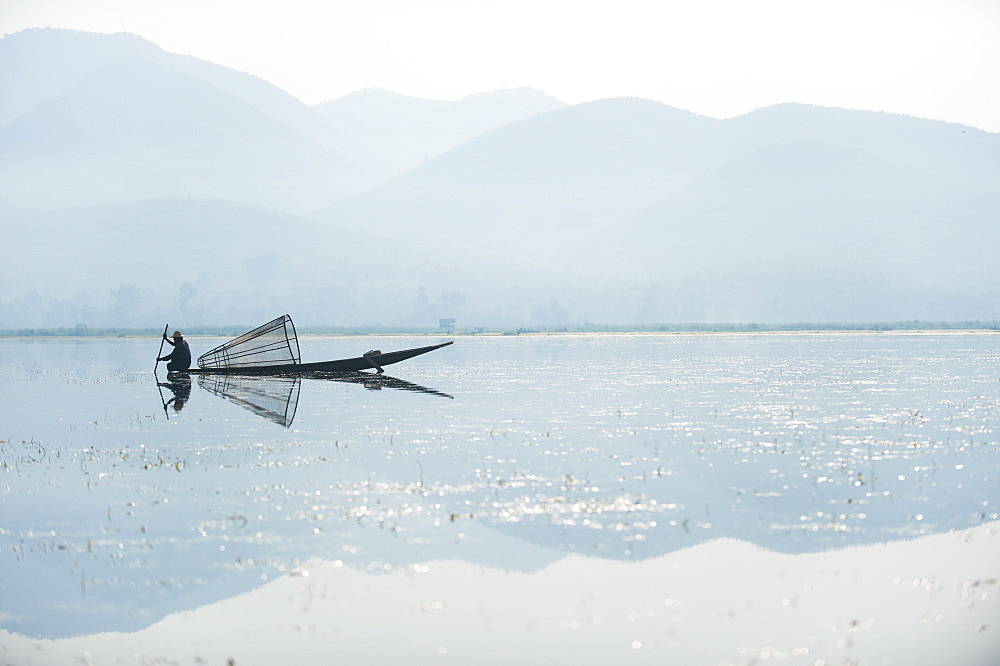 A basket fisherman on Inle Lake scans the still and shallow water for signs of life, Shan State, Myanmar (Burma), Asia