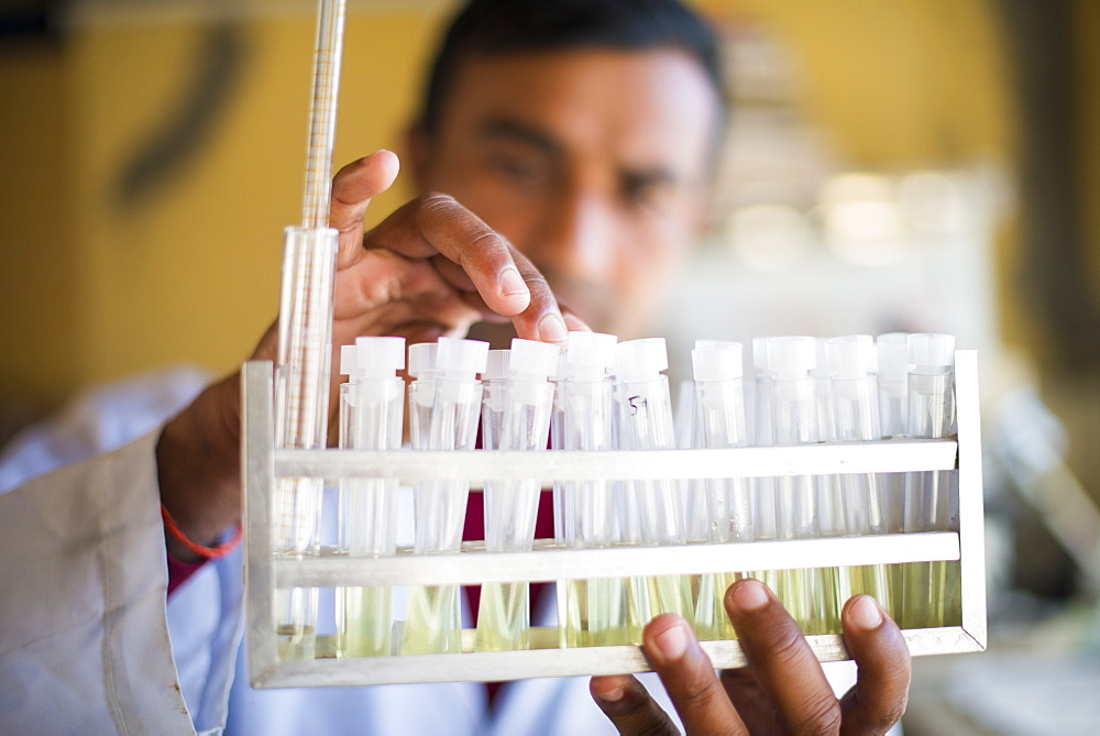 A lab technician working in a laboratory in a small hospital in Nepal holds a rack of test tubes, Jiri, Solu Khumbu, Nepal, Asia