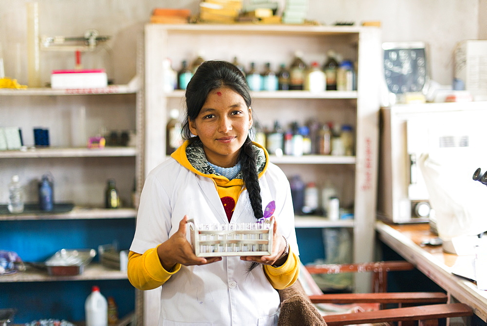 A young lab technician in a hospital in Nepal holds a rack of test tubes, Diktel, Khotang District, Nepal, Asia