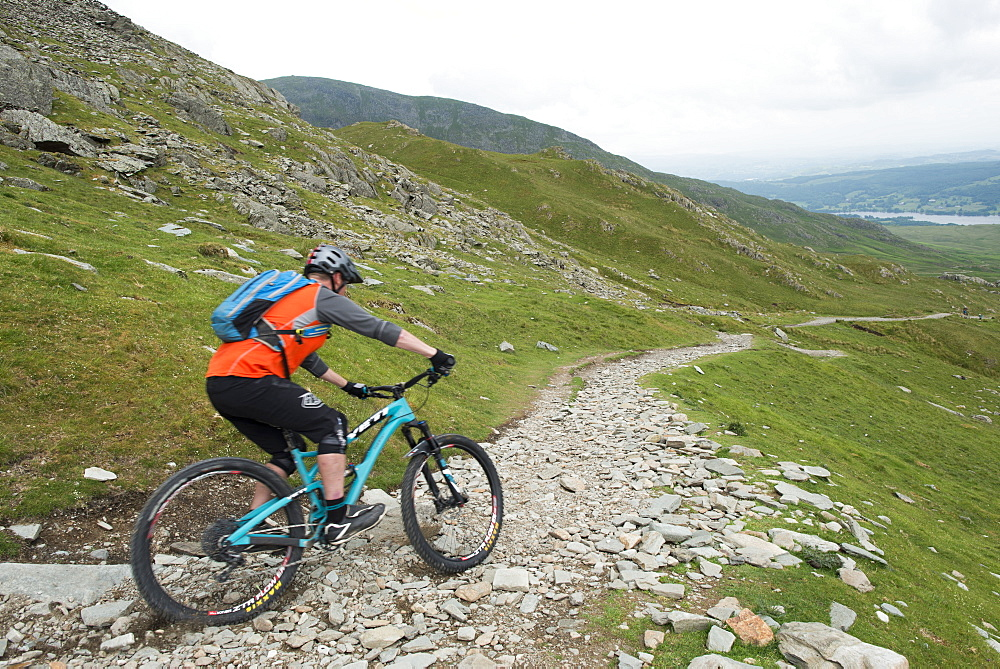 A mountain biker descends the trail from The Old Man of Coniston in the Lake District National Park, Cumbria, England, United Kingdom, Europe