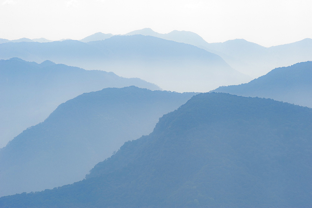 Foothills of the Himalayas in east Bhutan take on an ethereal appearance in early morning mist, Bhutan, Asia