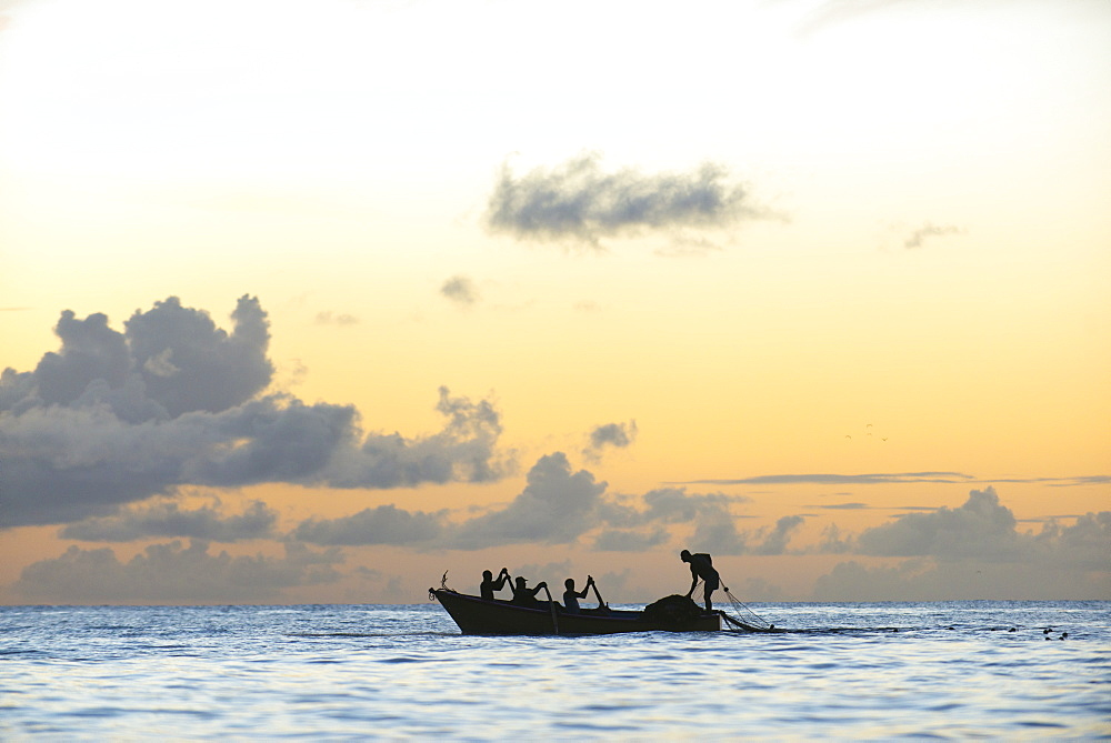 Seine fisherman lay their nets from a boat in Castara Bay in Tobago at sunset
