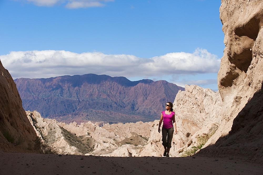 A girl walks through the stunning rock formations of the Quebrada de las Flechas, Argentina, South America