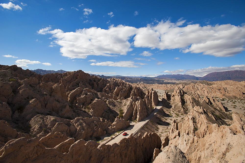 A car passes through the stunning rock formations of the Quebrada de las Flechas, Argentina, South America