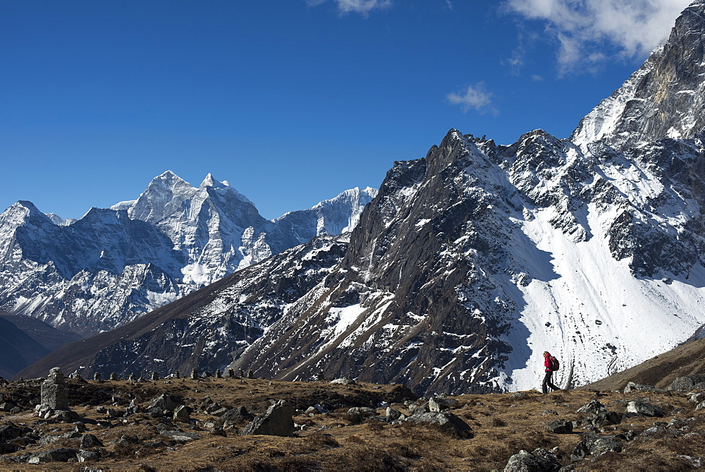 A trekker in the Everest region on the way up to Everest Base Camp seen here walking in front of Cholatse, Khumbu Region, Nepal, Himalayas, Asia