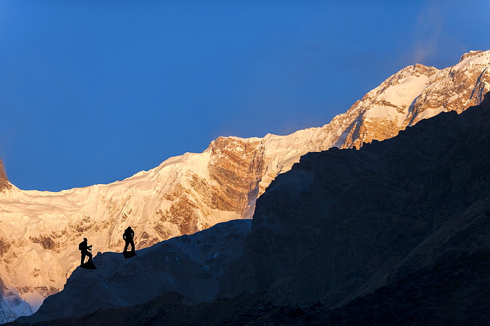 Trekkers climb to the top of the lateral morraine beside the Annapurna glacier to get a better view of Annapurna 1 in Nepal, the