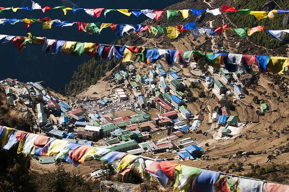 Buddhist prayer flags frame Namche Bazaar in the Khumbu Region, Nepal, Himalayas, Asia