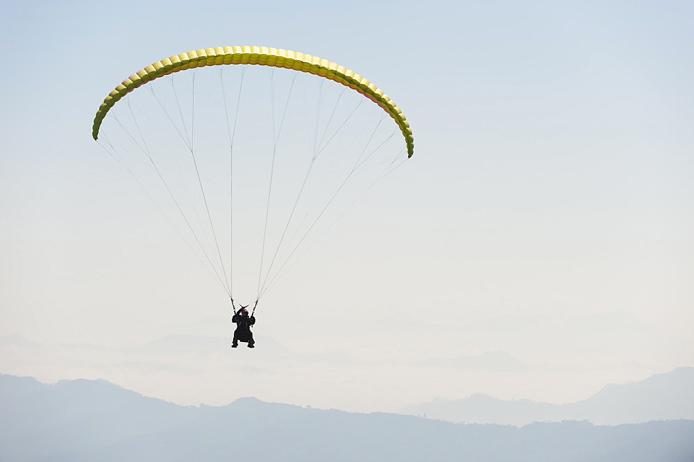 Paraglider flies above Pokhara, Nepal, Himalayas, Asia