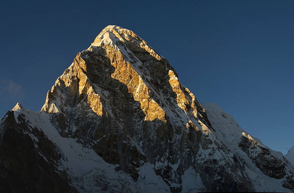 Sunset brings out the dramatic shape of Pumori, seen here from Kala Patar, Khumbu, Himalayas, Nepal, Asia