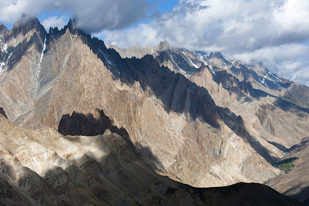 Light and shadow move across the jagged peaks of the Zanskar range seen from the top of the Dung Dung La in Ladakh, Himalayas, India, Asia