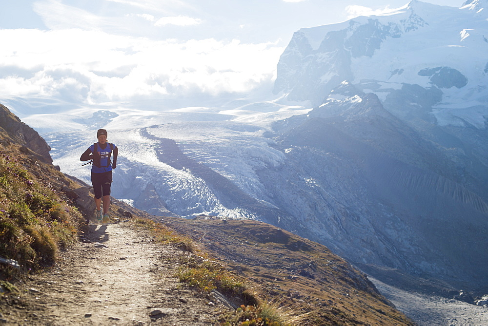 Running a trail in the Swiss Alps near Zermatt with a view of Monte Rosa in the distance, Zermatt, Valais, Switzerland, Europe