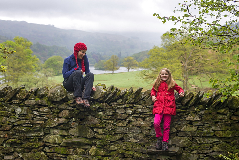Mother and daughter rest on a dry stone wall while on holiday in British Lake District