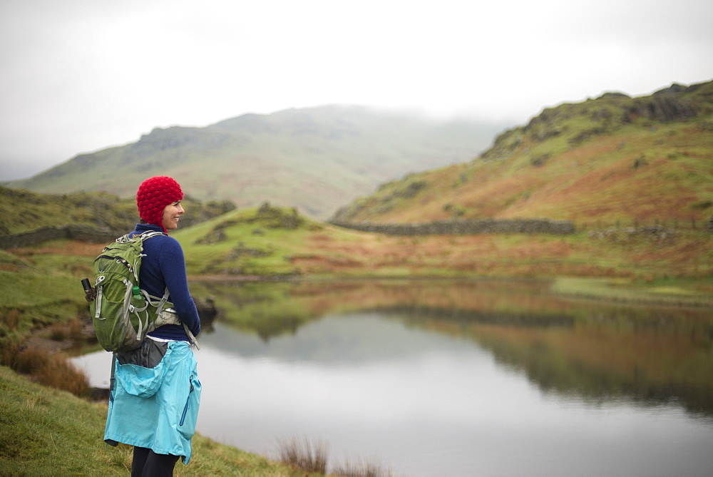 A woman looks out over Alcock Tarn near Grasmere in The Lake District in England