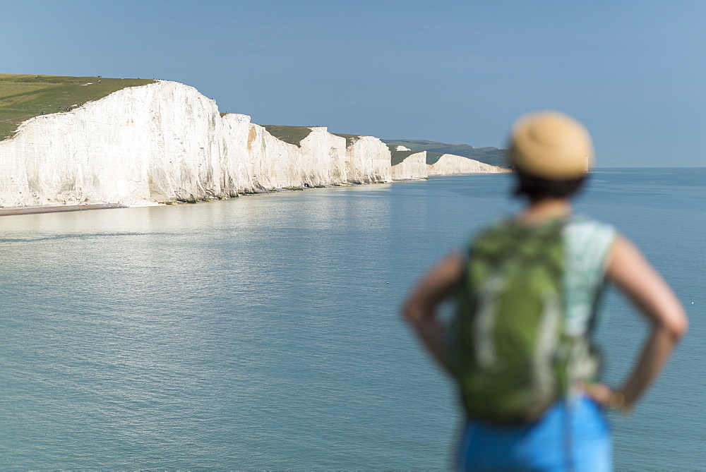 A woman looks towards the Seven Sisters while walking the South Downs Way in Sussex in England