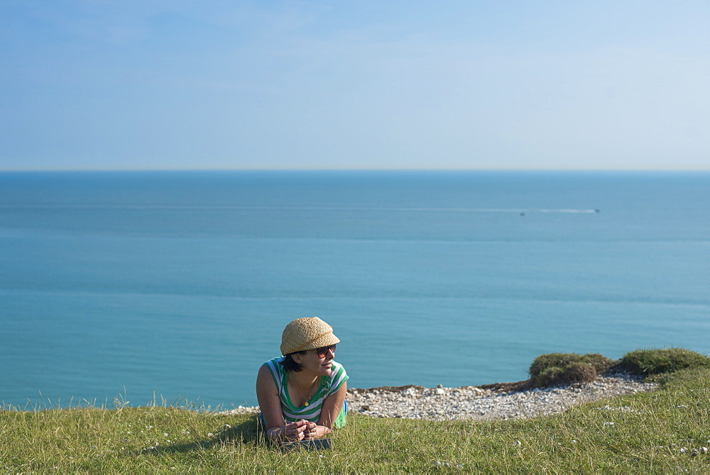 A woman lies on the cliffs near Beachy Head with views of the sea in the distance in England